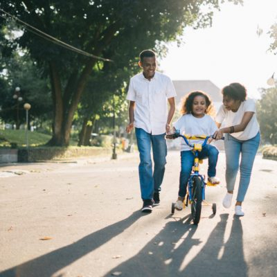Family therapy child learning to ride bike with parents